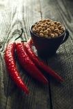Chili Peppers e tazza organici dei fagioli della soia su una tavola di legno fotografia stock