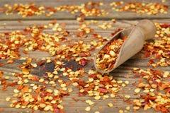 Chili Peppers Flakes And Corns macinato sul bordo di legno fotografia stock libera da diritti