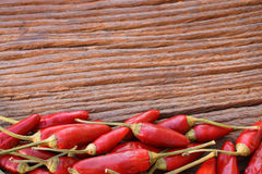 Chili peppers frame background. Fresh hot red chili peppers with border at the lower side as a frame on a rustic wooden background Royalty Free Stock Photo
