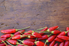 Chili peppers frame background. Fresh hot red chili peppers with border at the lower side as a frame on a rustic wooden background Stock Images