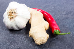 Chili peppers, garlic and ginger on a black background Royalty Free Stock Image