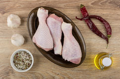 Chili peppers, garlic, vegetable oil and raw chicken legs Royalty Free Stock Images
