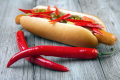 Chili peppers with hot dog. Red chili peppers with hot dog on gray wooden surface Royalty Free Stock Photo