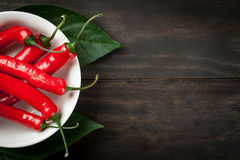 Chili Peppers. Hot chili peppers on white plate on wooden table background with copy space. Top view stock photos
