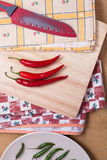 Chili peppers and knife on chopping board Royalty Free Stock Image