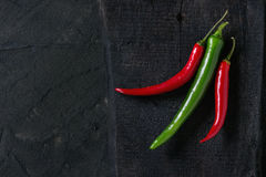 Chili peppers over black Royalty Free Stock Photos