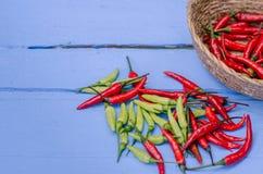 Chili Peppers rojo y verde en cuenco en fondo de madera Imagenes de archivo