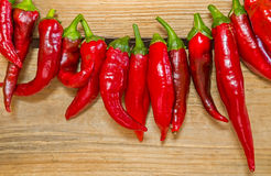 Chili peppers strung. On old wood background Stock Image