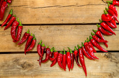 Chili peppers strung. On old wood background Royalty Free Stock Photos