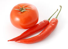 Chili peppers and a tomato Stock Photo