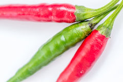 Chili peppers. Triad with two red and one green chili Stock Photos