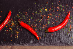 Chili peppers. Whole and crushed red chili peppers on wood Stock Images