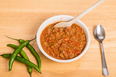Chili with Peppers and Wood Spoon Royalty Free Stock Photography