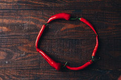 Chili peppers on a wooden background.  Royalty Free Stock Images