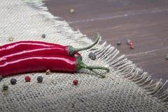 Chili pieprz kłama na parciaku na drewnianym stole Zdjęcie Stock