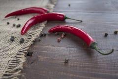 Chili pieprz kłama na parciaku na drewnianym stole Fotografia Stock