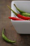 Chili pieprz w białej filiżance na drewno stole Obrazy Stock
