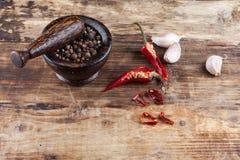 Chili pieprz z czarnym pepperand czosnkiem na drewnianym stole Zdjęcie Stock
