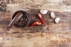 Chili pieprz z czarnym pepperand czosnkiem na drewnianym stole Obrazy Stock