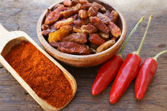 Chili pods, dried chili peppers and powder. Fresh red Chili pods, dried chili peppers and powder on wooden scoop on an old rustic wooden table Royalty Free Stock Photo