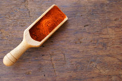 Chili powder on a spice scoop. Red hot chili powder on a wooden spice scoop with copy space on a rustic wooden table Royalty Free Stock Images