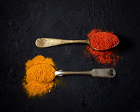 Chili powder and turmeric in a vintage spoon on a dark background Royalty Free Stock Images