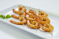 Chili prawn skewers. Spicy chili prawn skewers on a white plate Stock Photos