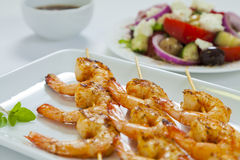 Chili prawn skewers close-up. Spicy chili prawn skewers with a traditional Greek salad and dressing Stock Photos