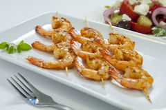 Chili prawn skewers with greek salad. Spicy chili shrimp skewers with a traditional Greek salad Royalty Free Stock Images