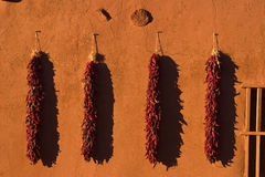Chili ristras hanging on Old Adobe Wall at sunset. Chili ristras are drying after harvest. This old Adobe wall is hand made with adobe from the site. Notice the Stock Photo
