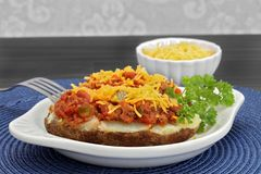 Chili stuffed baked potato. With a side of shredded cheese and garnished with parsley Royalty Free Stock Photography