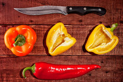 Chili and sweet peppers with knife Stock Images