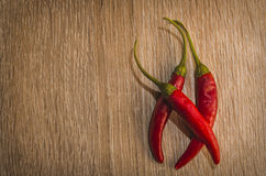 Chili. Three red chilies on wood background Stock Images