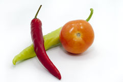 THE CHILI AND TOMATO IN FOCUS. ISOLATED FOCUS OF TOMATO AND CHILI OVER WHITE BACKGROUND Stock Photography