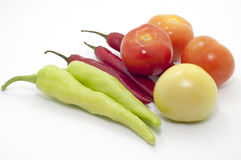 THE CHILI AND TOMATO IN FOCUS. ISOLATED FOCUS OF TOMATO AND CHILI OVER WHITE BACKGROUND Stock Image