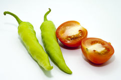 THE CHILI AND TOMATO IN FOCUS. ISOLATED FOCUS OF TOMATO AND CHILI OVER WHITE BACKGROUND Royalty Free Stock Photography