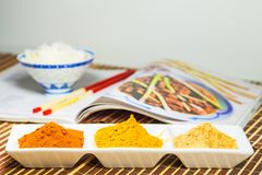 Chili, turmeric, ginger powder in bowls with cookbook. In the background Royalty Free Stock Photos
