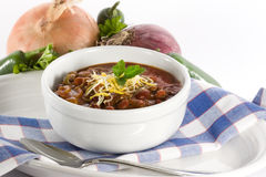 Chili in White Bowl. Chili con carni topped with monterrey jack and cheddar cheeses, and fresh sprig of cilantro, served in white bowl on blue and white linen royalty free stock image