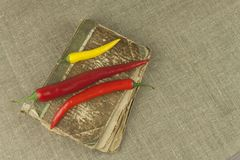 Chilies with an old recipe book. Vegetables ready for home cooking. Stock Photos