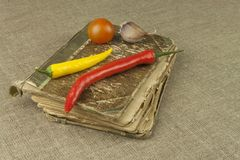 Chilies with an old recipe book. Vegetables ready for home cooking. Stock Photo