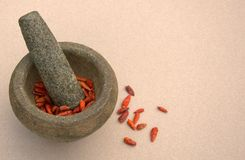 Chilies in Stone Bowl. This photo shows sun dried Birds Eye chilies in a stone pestle/mortar bowl ready for use in the kitchen royalty free stock images