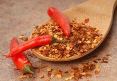 chiliflakes pepprar den röda skeden för peppar royaltyfri bild