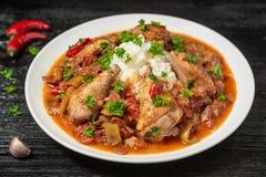 Chilindron del pollo con la salsa vegetal gruesa con el vino rojo y el jamón seco-curado imagenes de archivo