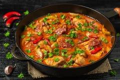 Chilindron del pollo con la salsa vegetal gruesa con el vino rojo y el jamón seco-curado La visión desde la tapa Copia-espacio fotografía de archivo
