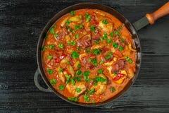 Chilindron del pollo con la salsa vegetal gruesa con el vino rojo y el jamón seco-curado La visión desde la tapa Copia-espacio imágenes de archivo libres de regalías