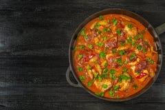 Chilindron del pollo con la salsa vegetal gruesa con el vino rojo y el jamón seco-curado La visión desde la tapa Copia-espacio foto de archivo libre de regalías