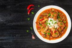 Chilindron del pollo con la salsa vegetal gruesa con el vino rojo y el jamón seco-curado La visión desde la tapa Copia-espacio imagenes de archivo