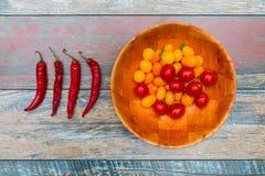 Chilipeppar och bunke av tomater på trätabellen Arkivfoto