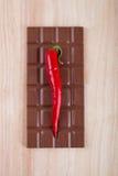 Chilipeppar och choklad på skärbräda Arkivfoton