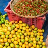 Chilipeppar och limefrukt som är till salu på den asiatiska marknaden Arkivfoton
